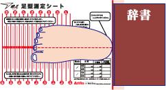 測定シートのかかと線上に厚みのあるもの(辞書やティッシュケースなど)を置いて、片足のかかとを合わせます。かかとの中心と人差し指(第2指)を紙の目盛り線に